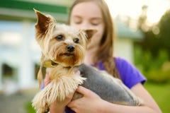 Petite fille mignonne tenant son chien drôle de terrier de Yorkshire Photographie stock libre de droits