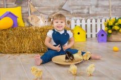 Petite fille mignonne utilisant les jeans rustiques jouant le cache-cache avec un poulet se reposant à une meule de foin Le conce photo stock