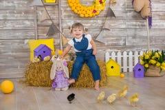 Petite fille mignonne utilisant les jeans rustiques jouant le cache-cache avec un poulet se reposant à une meule de foin Le conce images libres de droits
