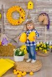 Petite fille mignonne utilisant les jeans rustiques jouant le cache-cache avec un poulet se reposant à une meule de foin Le conce images stock