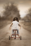 Petite fille montant loin sur son tricycle Photo stock
