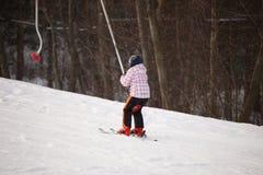 Petite fille montant par le levage de ski Photographie stock