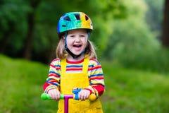 Petite fille montant un scooter coloré Photo libre de droits