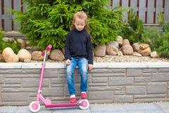 Petite fille montant un scooter dans sa cour Photos stock