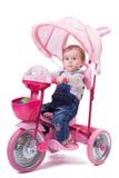Petite fille montant un tricycle d'enfants Images stock