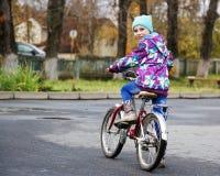 Petite fille montant une bicyclette en parc d'automne photos libres de droits
