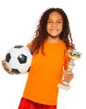 Petite fille noire tenant le ballon de football et le prix Photos stock