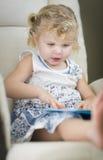 Petite fille observée par bleu d'une chevelure blond lisant son livre Image libre de droits