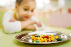 Petite fille observant sur le caramel de sucre dans le plat Images stock