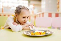 Petite fille observant sur le caramel de sucre dans le plat Photos libres de droits