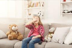 Petite fille occasionnelle effrayée regardant la TV tout en se reposant sur le sofa à la maison Image stock