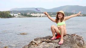 Petite fille ondulant avec le drapeau grec sur la plage Corfou Grèce banque de vidéos