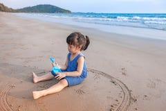 Petite fille 2 ou 3 ans de jeux sur la plage dans le coucher du soleil Image libre de droits