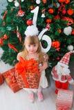 Petite fille ouvrant un cadeau à la maison dans le salon Image stock