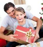 Petite fille ouvrant un cadeau de Noël Photo libre de droits
