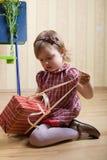 Petite fille ouvrant un cadre avec le cadeau Image libre de droits