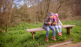 Petite fille parlant à l'oreille du garçon se reposant dessus Photo stock