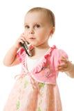 Petite fille parlant au téléphone dans une robe rose Images stock