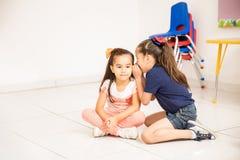 Petite fille partageant un secret à l'école Photo stock