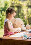 Petite fille peignant extérieure avec son ami d'ours de nounours Photo stock