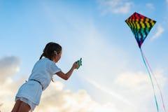 Petite fille pilotant un cerf-volant Photos stock