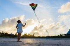 Petite fille pilotant un cerf-volant Images libres de droits