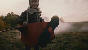 Petite fille pilote courant dans l'avion de carton d'amusement avec de la fumée de couleur derrière sur le mouvement lent d'autom clips vidéos