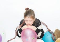 Petite fille pleurante bouleversée avec des ballons sur le fond blanc et gris Image stock