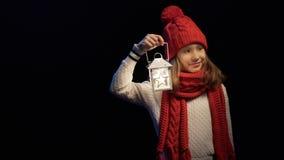 Petite fille portant l'éclairage tricoté de chapeau et d'écharpe d'hiver avec la lanterne clips vidéos