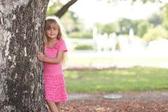 Petite fille posant derrière l'arbre image stock