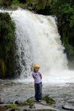 Petite fille près de cascade à écriture ligne par ligne de montagnes Photos stock