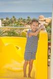 Petite fille près des glissières de parc aquatique Photo stock