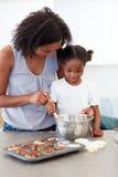 Petite fille préparant des biscuits avec sa mère photo libre de droits