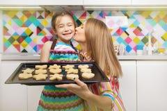 Petite fille préparant un biscuit sur la cuisine pour sa mère Photographie stock