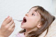 Petite fille prenant la médecine avec la cuillère photo stock