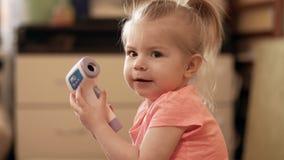 Petite fille prenant la température utilisant un thermomètre numérique à l'intérieur dans 4k banque de vidéos