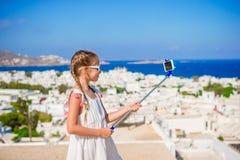 Petite fille prenant la ville de Mykonos de fond de selfie en Grèce Images stock