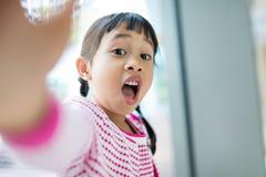 Petite fille prenant le selfie avec l'expression du visage drôle photo libre de droits