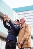 Petite-fille prenant le selfie avec le grand-père Images stock