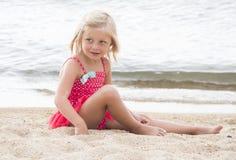 Petite fille prenant un bain de soleil sur la plage Images stock
