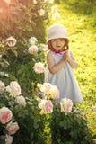 Petite fille priant à un dieu Enfant se tenant aux fleurs roses de floraison sur l'herbe verte photo libre de droits