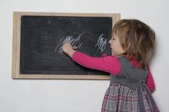 Petite fille près de tableau noir Photographie stock