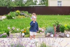 Petite fille réfléchie d'enfant en bas âge dans de grandes espadrilles se tenant sur la cour d'une belle maison Photo stock