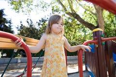 Petite fille réfléchie jouant dans le terrain de jeu Images libres de droits