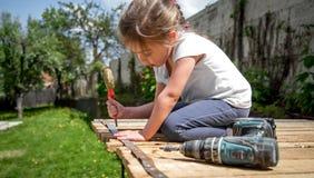 Petite fille réparant avec le tournevis et le tournevis à disposition Photographie stock