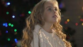 Petite fille rêvant du cadeau de Noël, se reposant sur le fond lumineux clips vidéos