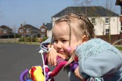 Petite fille rêvant sur le vélo Photographie stock libre de droits