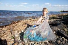 Petite fille rassemblant des déchets image stock