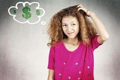 Petite fille rayant le chef pensant comment gagner l'argent photographie stock
