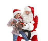 Petite fille recevant le cadeau de Santa Claus authentique sur le fond blanc image libre de droits